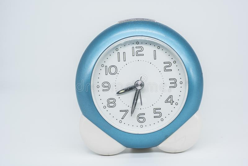 Small alarm clock with blue border over white background royalty free stock photo