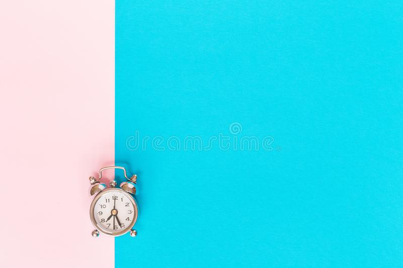 Small alarm clock on blue white background stock photo