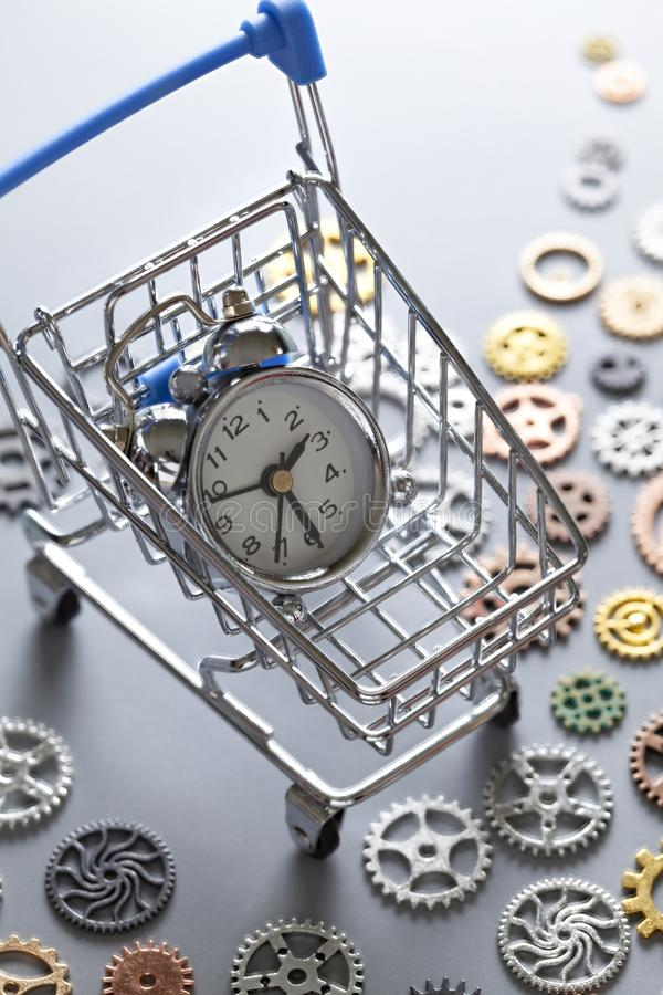 Small alarm clock in shopping cart and small parts of watch. On gray table stock images