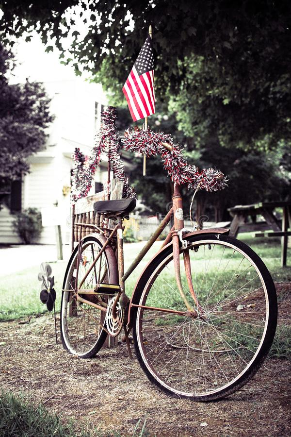 American Flag on old bike. A small American flag and red white and blue garland adorn an old bicycle royalty free stock image