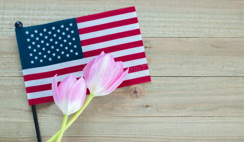 Small American flag with pink tulips on a wood background stock images