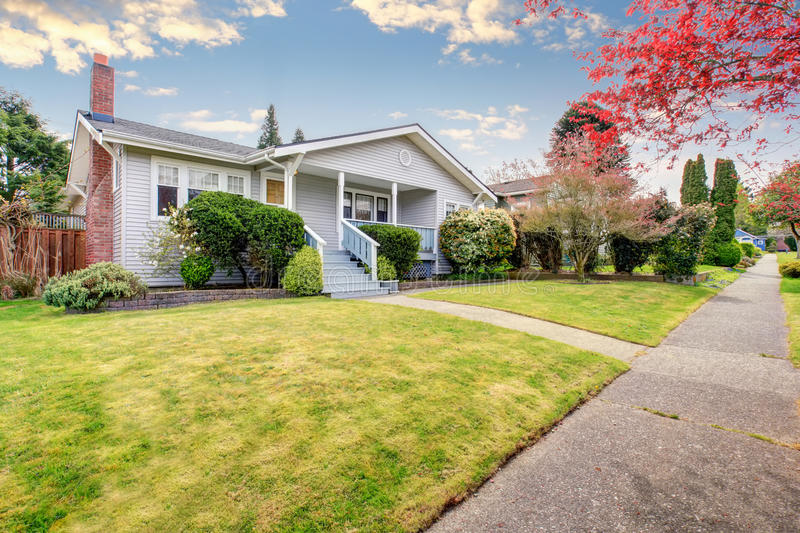 Small American home with light exterior and white trim. Small American home with light exterior and a large grass filled lawn stock image