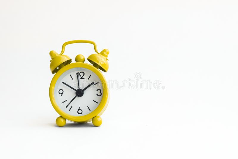 Small analogue yellow golden clock in isolated white background.  stock photos