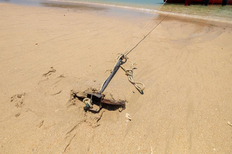 Small Anchor in Beach Sand for Parking Tourism Boat in the Island.  royalty free stock image