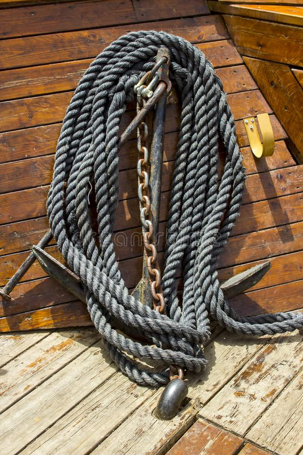 A small anchor, chain and rope stowed safely on a small boat. A small anchor, chain and rope stowed safely and neatly on a traditional wooden tourist boat on the stock photography