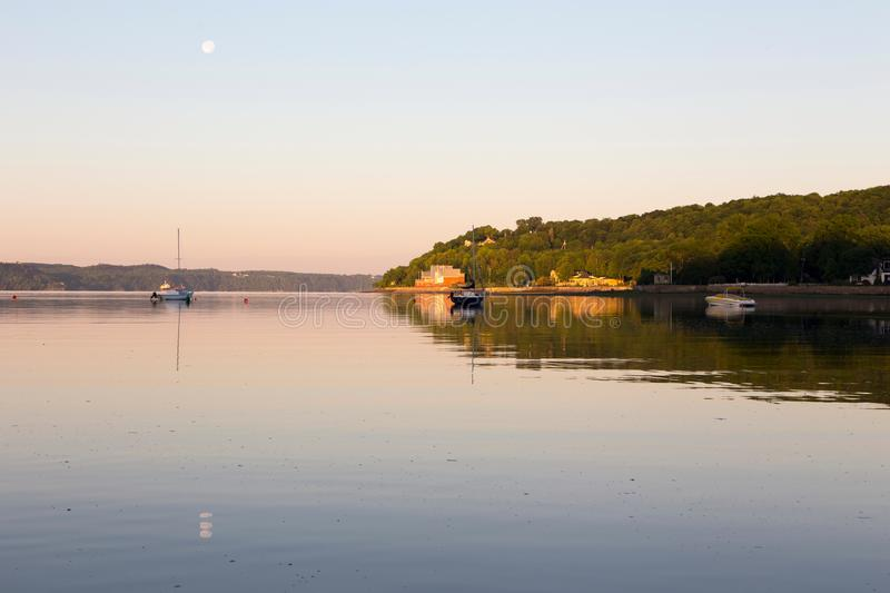 Small anchored sailboats and speedboat in the St. Lawrence River during an beautiful early summer morning stock images