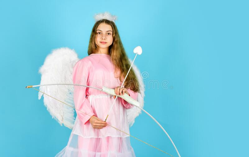 Small angel. girl cupid hold bow and arrow. cupids arrow hit right in heart. love and romance. happy valentines day royalty free stock images