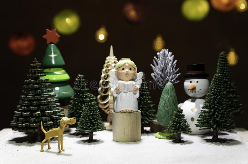 Small Angel read a book on circle wooden chair with dog watching and snow man isolated from Christmas light background royalty free stock images