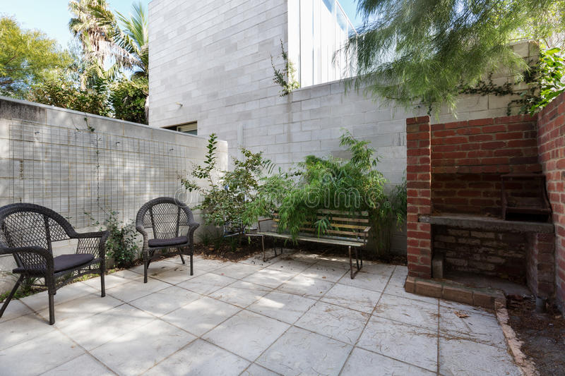 Small apartment courtyard with paving and cane outdoor chairs. Small Australian apartment courtyard with paving and cane outdoor chairs stock image