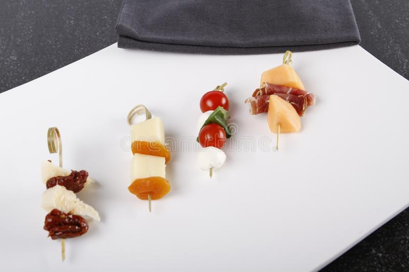 Small appetizers with cheeses, fruits and tomatoes on sticks. Small appetizers with cheeses, fruits and tomatoes, dried ham on wooden sticks served on a plate stock images