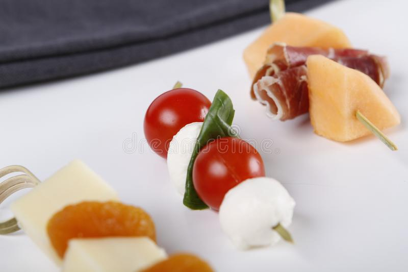 Small appetizers with cheeses, fruits and tomatoes on sticks. Small appetizers with cheeses, fruits and tomatoes, dried ham on wooden sticks served on a plate royalty free stock image