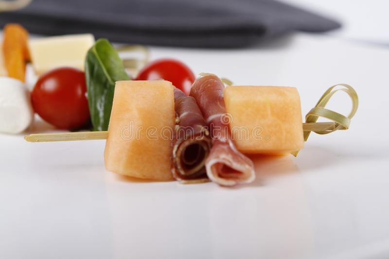 Small appetizers with cheeses, fruits and tomatoes on sticks. Small appetizers with cheeses, fruits and tomatoes, dried ham on wooden sticks served on a plate stock photos