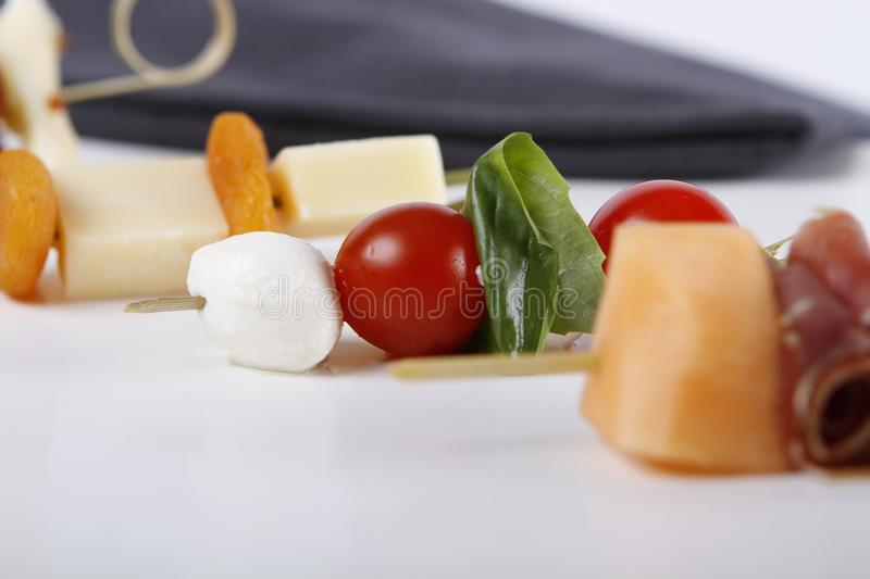 Small appetizers with cheeses, fruits and tomatoes on sticks. Small appetizers with cheeses, fruits and tomatoes, dried ham on wooden sticks served on a plate stock photo