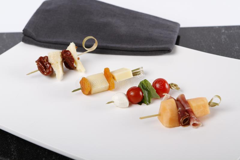 Small appetizers with cheeses, fruits and tomatoes on sticks. Small appetizers with cheeses, fruits and tomatoes on wooden sticks served on a plate stock photos