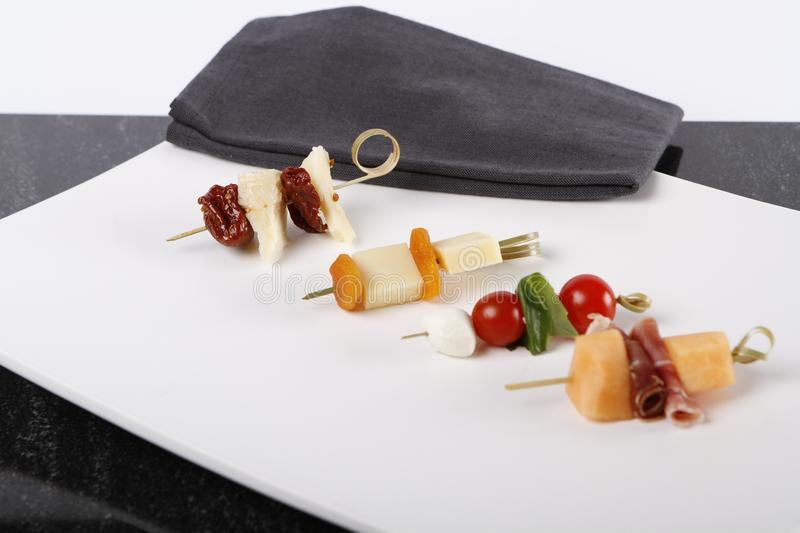 Small appetizers with cheeses, fruits and tomatoes on sticks. Small appetizers with cheeses, fruits and tomatoes on wooden sticks served on a plate stock photo