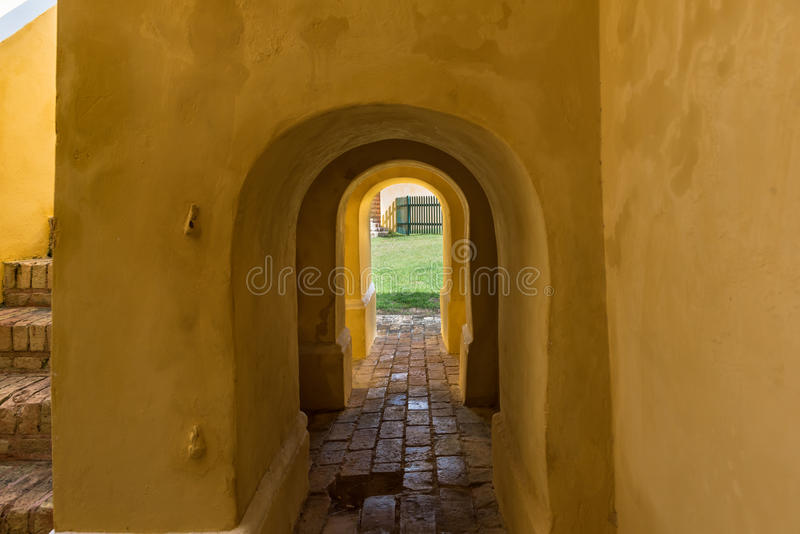 Small arched passageway to the center courtyard in fortress. Cobblestone pathway. Brick stairs to the second floor stock photography