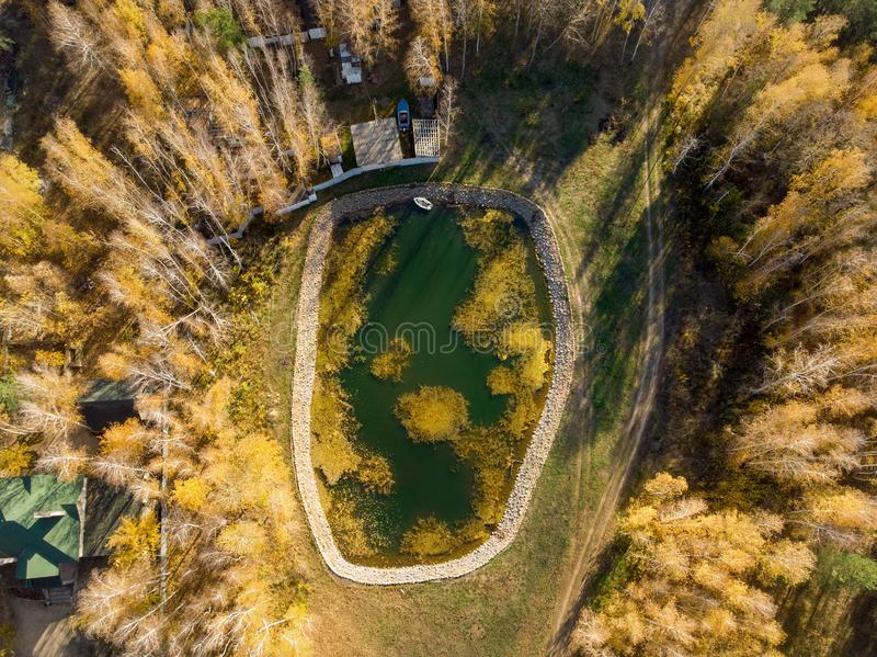 Small artificial reservoir pond for fishing with boat surrounded by golden autumn foret trees and cottage houses. Aerial drone stock photography