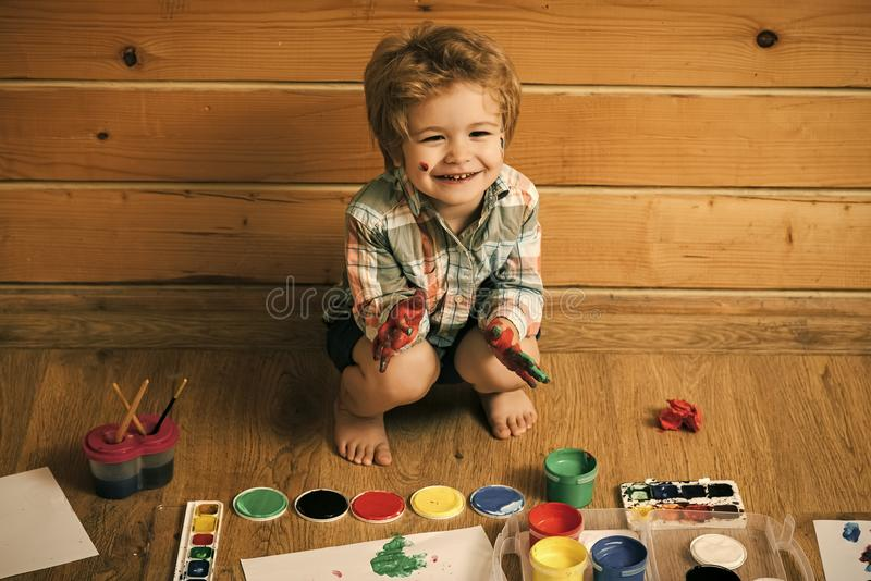 Small artist. Boy painter painting on wooden floor stock image