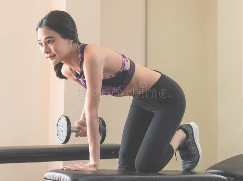 Small asian woman is lifting dumbbell in fitness. Club royalty free stock photos