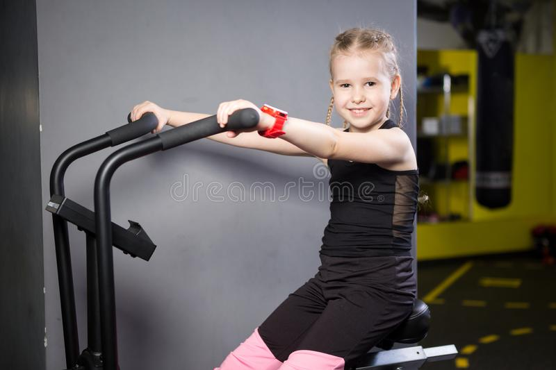 Small attractive caucasian child using exercise bike in the gym. Fitness. A little athlete using an air bike for a cardio workout stock images