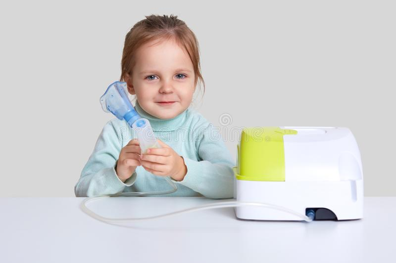 Small attractive girl makes inhalation with nebulizer, cures cough, sits at white desk against studio background. Compressor. Inhaler with mask. Little kid has stock photography