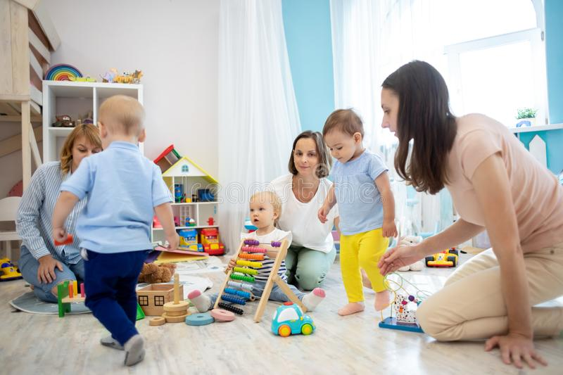 Small babies with their parents play in kindergarten stock photo