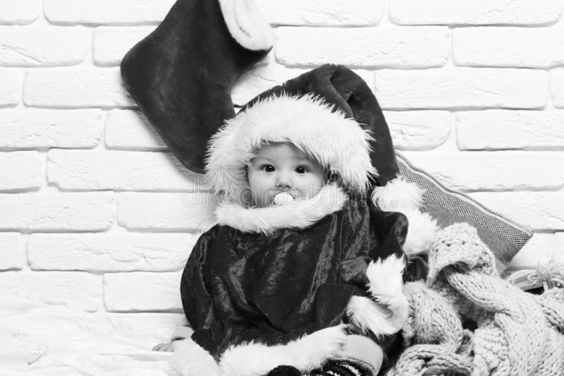 Small baby boy with adorable curious face in red sweater with dummy in new year hat and christmas or xmas stocking or royalty free stock photos