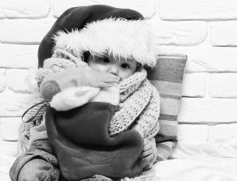 Small baby boy with adorable curious face in red sweater with dummy in new year hat scarf and christmas or xmas stocking. Or boot on white brick wall background royalty free stock images