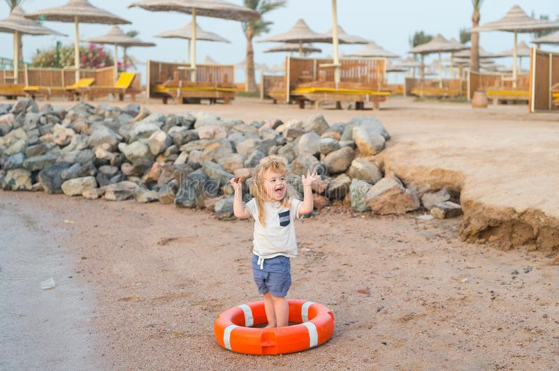 Small baby boy with happy face with lifebelt on beach stock photography