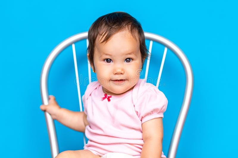 Small baby girl with dark hair and brown eyes mixed rase, kazakh girl and russian on blue background.  stock images