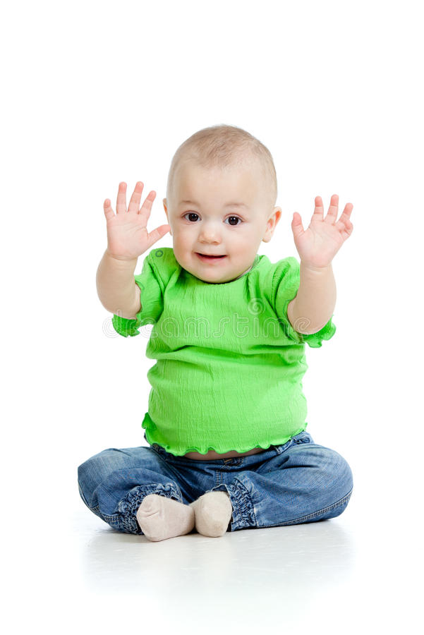 Small baby girl with raised hands sitting on floor. Small baby girl sitting on floor royalty free stock photography
