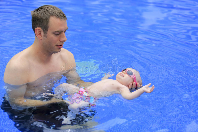 Small baby girl is swimming in the pool. With daddy for the first time. Three months old baby stock photos