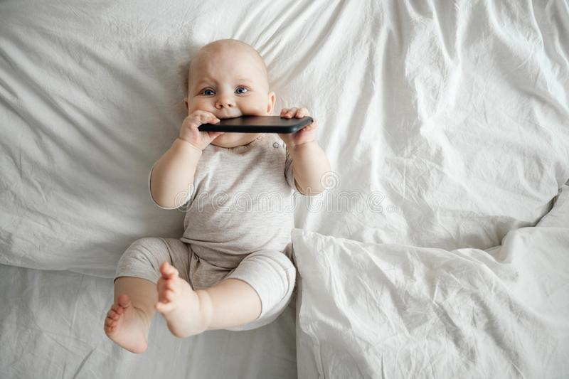 Small baby holds a smartphone and listens to music while lying on a bright bed. royalty free stock photo