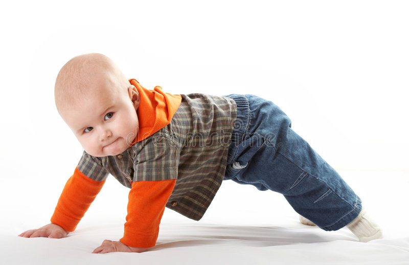 Small baby posing. Small baby in bright shirt doing gymnastics stock photography