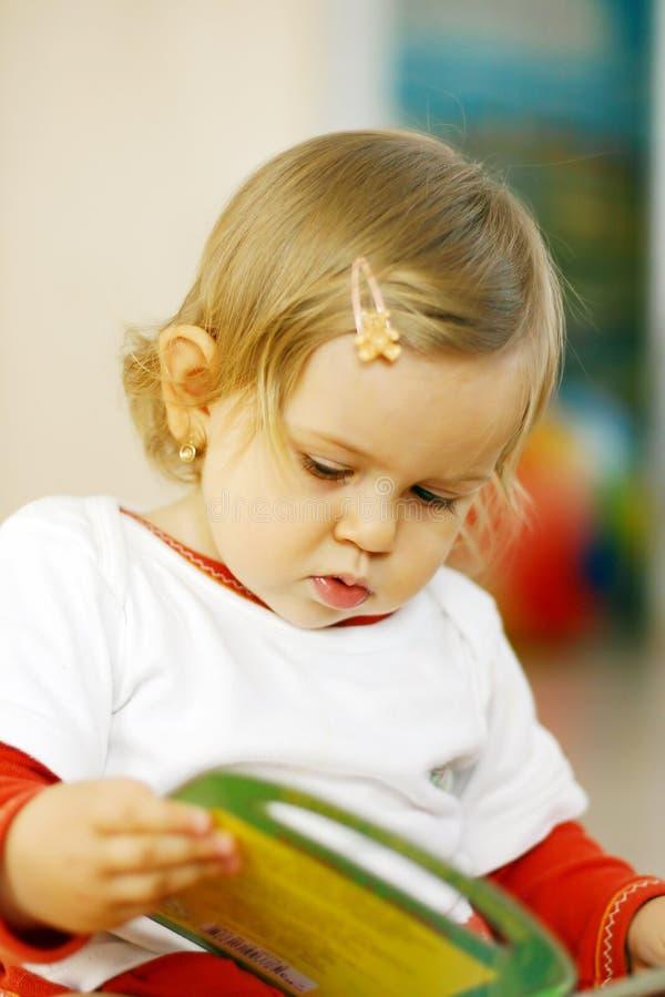 Small baby reading a book royalty free stock photos
