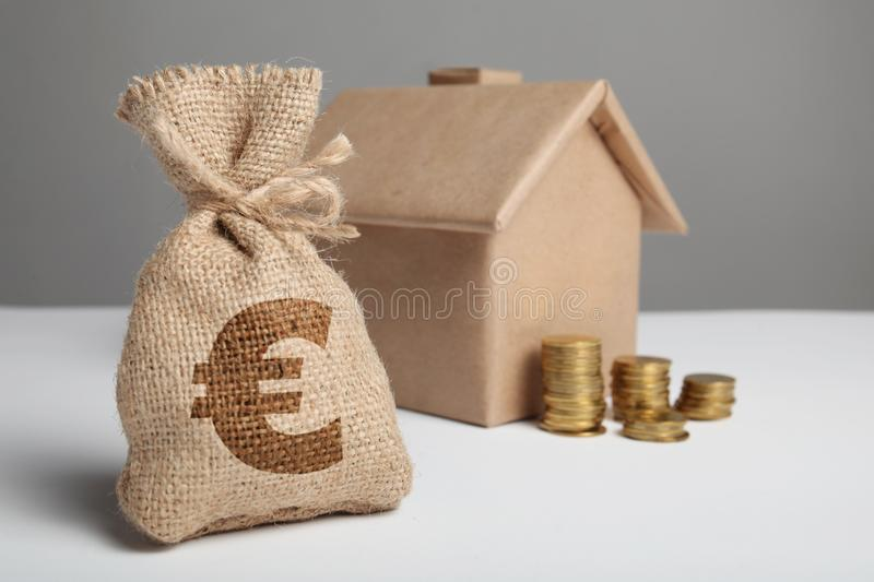 Small bag with money and euro sign. Stack of coins and house model. Mortgage financial property. Rising rent. House and coins royalty free stock photos