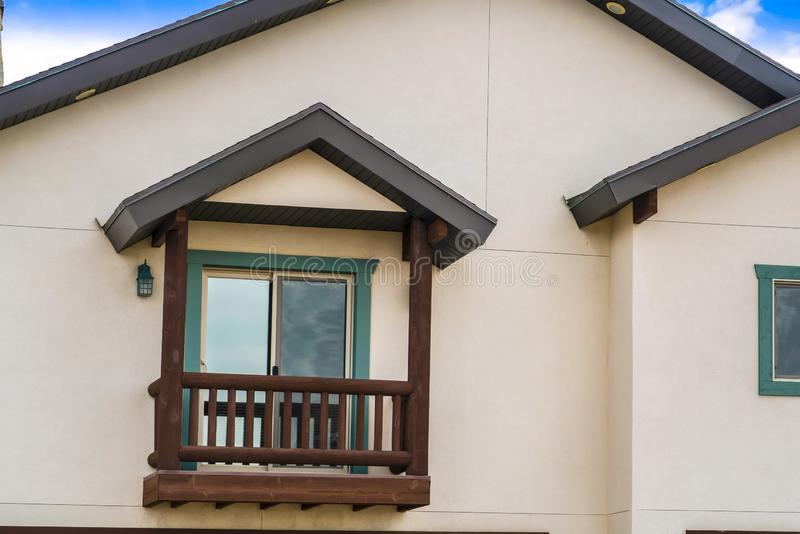 Small balcony with brown wooden railings and posts under a pitched roof. A shiny sliding glass door leads to the interior of this house stock photography