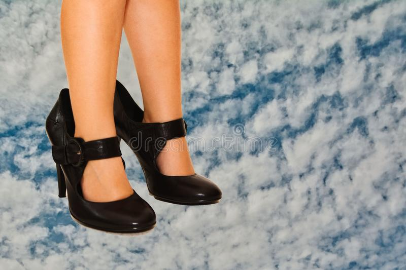 Small bare feet in big shoes stock photography