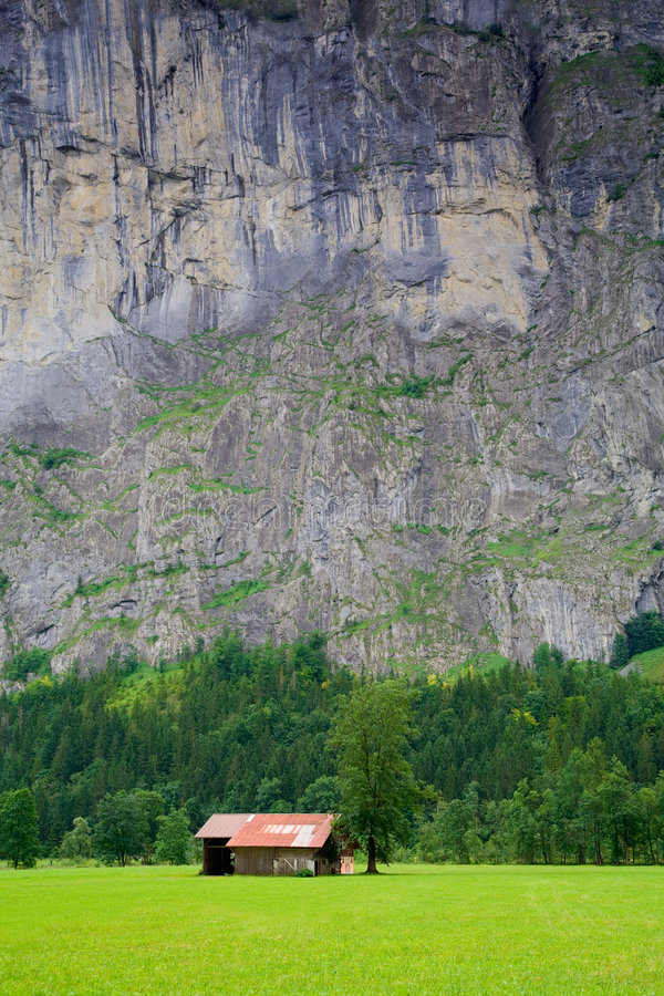 Small Barn close to a Steep Rocky Mountain. A small barn is close to a steep rocky mountain near Lauterbrunnen, Bern Canton, Switzerland stock image