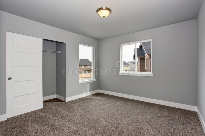 Small basement room interior with grey walls and white trim. The room with walk in closet royalty free stock images