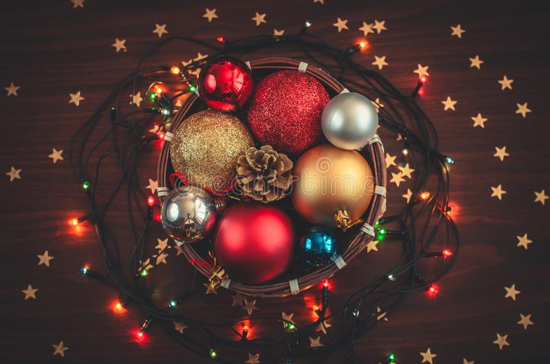 A small basket full of Christmas decorations, balls, a cone with glowing garland and golden stars confetti stock photos