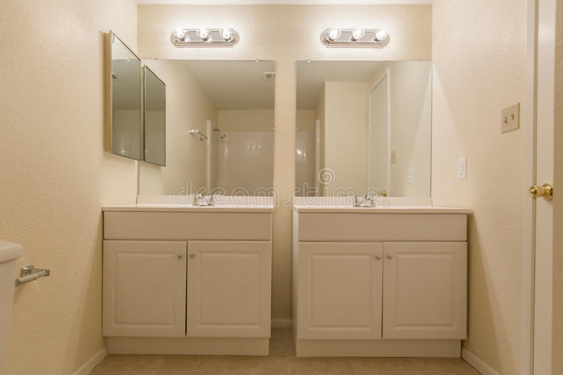Small Bathroom. With double sinks and mirrors royalty free stock photos