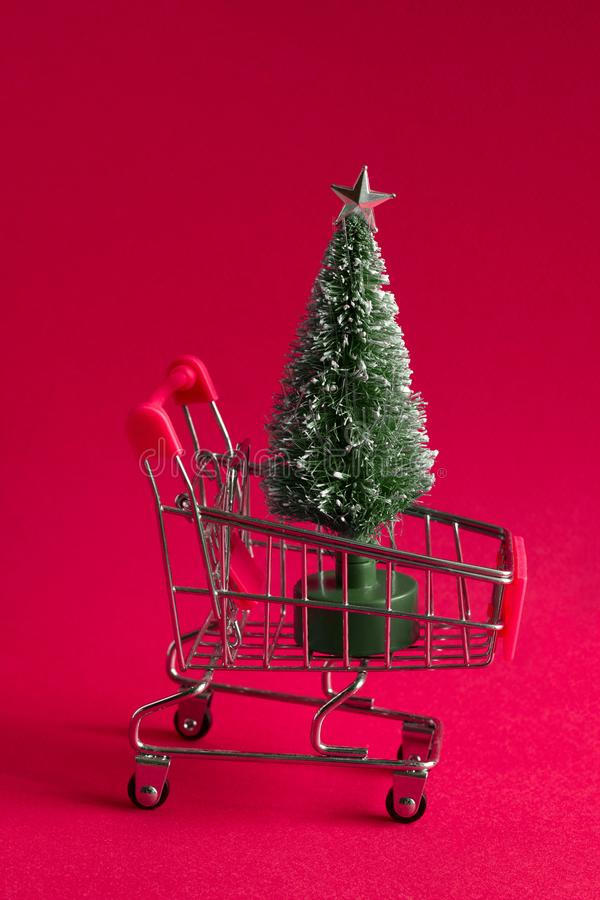 Bauble christmas tree in a shopping cart on a pink background, christmas and new year greeting card. Small bauble christmas tree in a shopping cart on a pink stock photos
