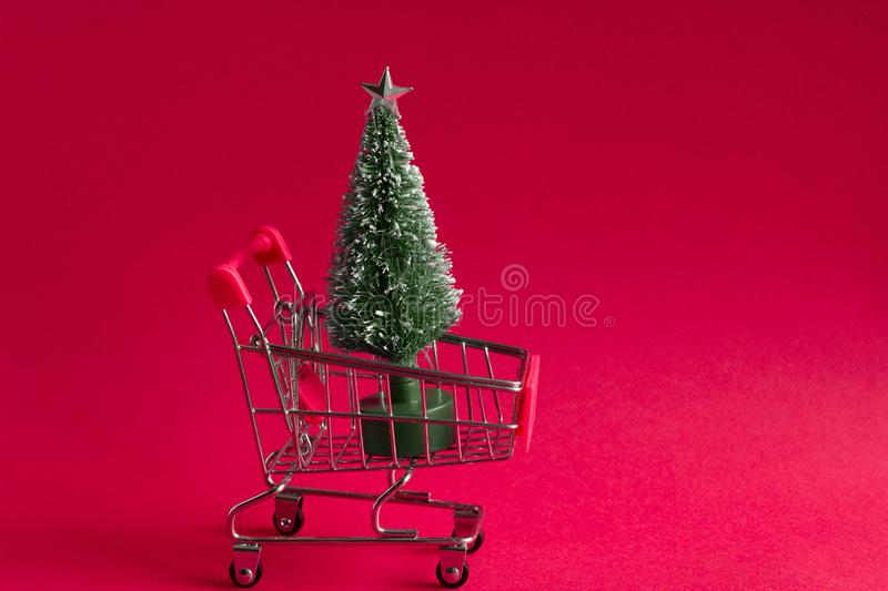 Bauble christmas tree in a shopping cart on a pink background, christmas and new year greeting card with copy space. Small bauble christmas tree in a shopping royalty free stock images