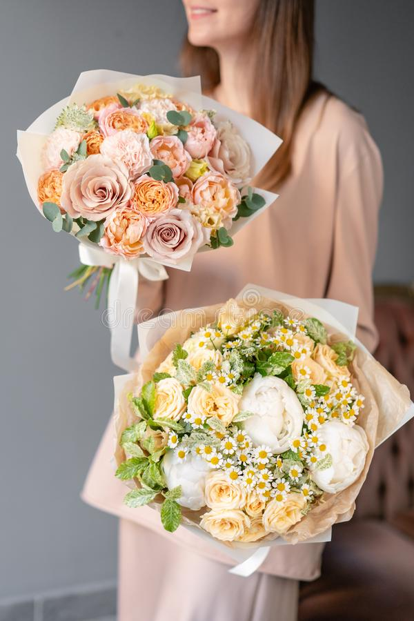 Two Small Beautiful bouquet of mixed flowers in woman hand. Floral shop concept. Flowers delivery royalty free stock images
