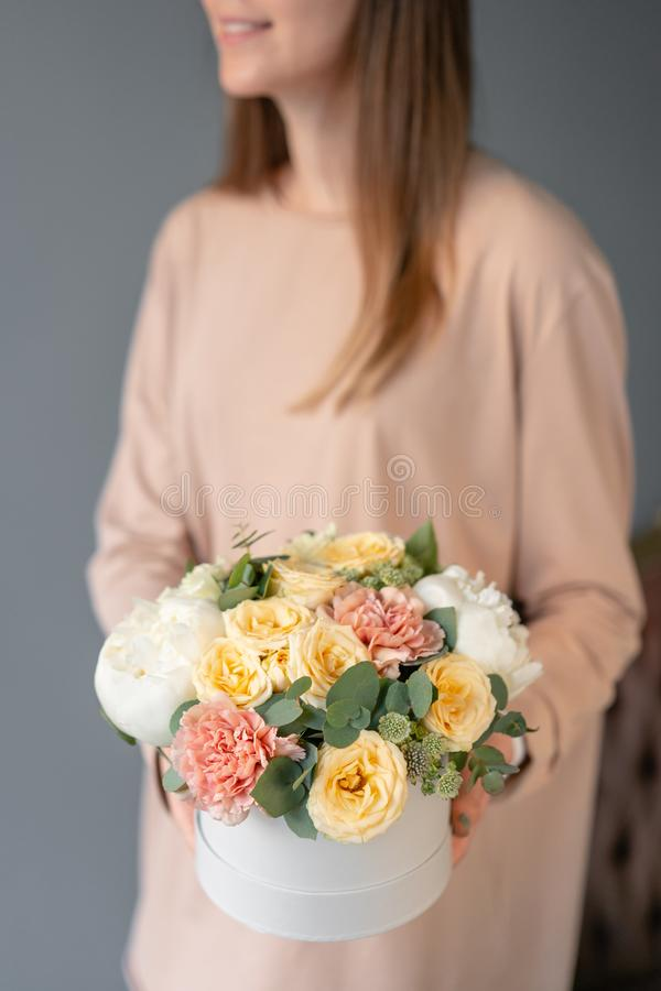 Small Beautiful bouquet in a round box. Bunch of mixed flowers in woman hand. Floral shop concept. Flowers delivery stock image