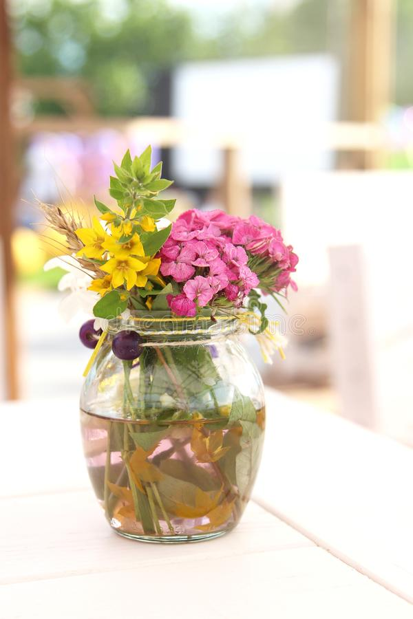 A small beautiful bouquet of summer flowers in a vase on a table. Composition royalty free stock photography