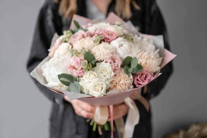 Small Beautiful bouquet of mixed flowers in woman hand. Floral shop concept. Flowers delivery. White peonies royalty free stock images