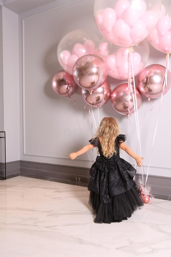 Small beautiful girl with blond curly hair in elegant dress holding air balloons,celebration holiday stock photo