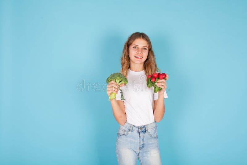Small beautiful girl holding a fresh radish healthy food royalty free stock image